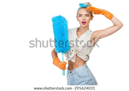 Cheerful girl is holding brush for dust. She is raising her hand to her forehead proudly. She has already done all housework. Isolated on background and copy space in left side - stock photo