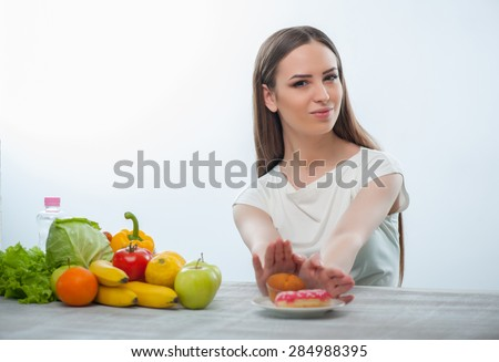 Cheerful girl is pushing away harmful donuts. She is looking at the camera seriously. The girl is sitting at the table on which there are a lot of healthy fruits and vegetables. Isolated on a white - stock photo