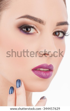 Cheerful girl is showing her beautiful make-up. She is touching her face with pleasure. The model is looking at camera with passion - stock photo