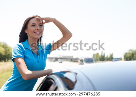 Cheerful girl is standing and leaning on her transport. She is raising her hand to her forehead. He is viewing something interesting and smiling. Copy space in right side - stock photo