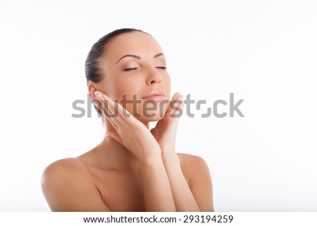 Cheerful girl is touching her cheeks with both her palms with pleasure. She is relaxed. Her eyes are closed. Isolated on white background and there is copy space in right side - stock photo