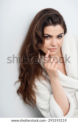 Cheerful girl is touching her lip with her finger attractively. Her look is enigmatic.  Isolated on a grey background - stock photo