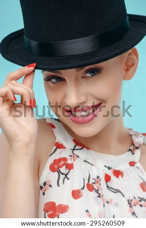 Cheerful girl is wearing big classic hat on her head. She is touching it and smiling. Isolated on blue background - stock photo
