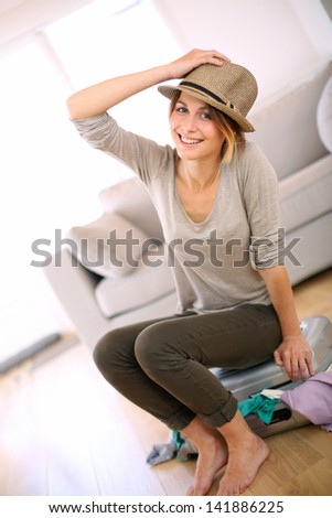 Cheerful girl leaving for vacation - stock photo