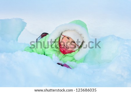 Cheerful girl lying in deep snow drift - stock photo