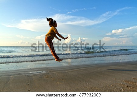 Cheerful girl on the beach at dawn. An Asian girl shown cheerful jumped in early morning. The shot taken at Hat Wanakorn Beach,Prachaup Khirikhan, Thailand.