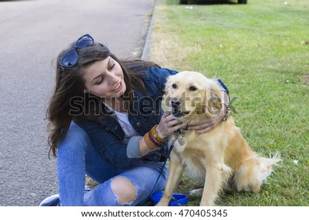 Cheerful girl on walk with golden retriever in summer