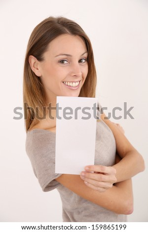 Cheerful girl on white background holding leaflet for message - stock photo