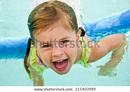 Cheerful girl playing in a swimming pool with a foam float