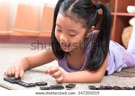 Cheerful girl playing  with domino game, lying on floor. - stock photo