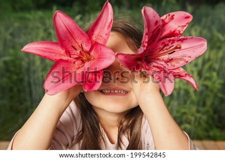 Cheerful girl playing with flowers, looking into the camera through the lily - stock photo