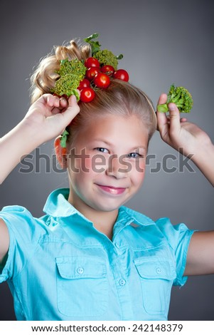 Cheerful girl posing with horns made of broccoli - stock photo