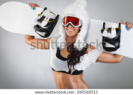 Cheerful girl posing with snowboard and fur hat - stock photo