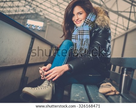 Cheerful girl putting on skates  on ice skating rink - stock photo