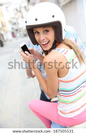 Cheerful girl riding motorcycle and using smartphone - stock photo