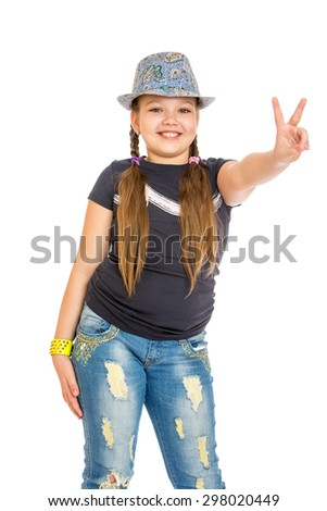 Cheerful girl schoolgirl in a hat and faded jeans shows the hand sign in Victoria-Isolated on white background - stock photo