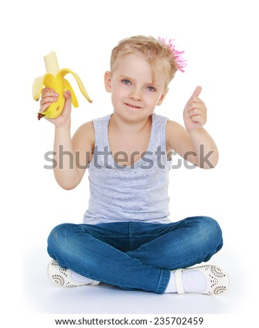 cheerful girl shows all super and she likes big tasty yellow banana.White background, isolated photo. - stock photo