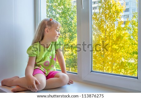 Cheerful girl sitting by the window - stock photo