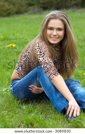 cheerful girl sitting on the green grass.