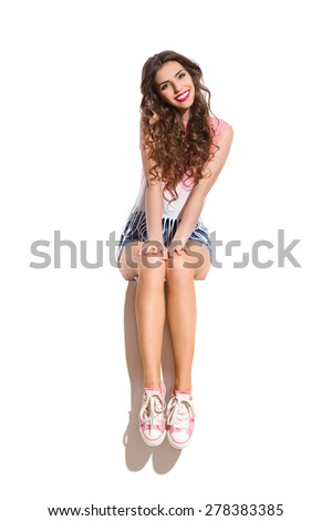 Cheerful Girl Sitting. Smiling young woman in pink sneakers sitting on the top of white banner. Full length studio shot isolated on white. - stock photo
