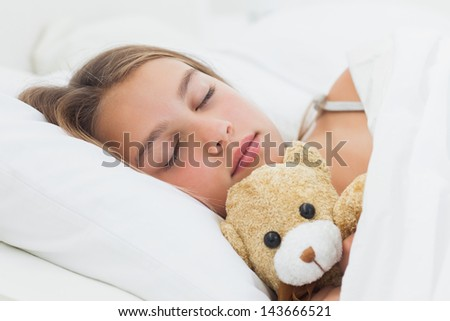 Cheerful girl sleeping with her teddy bear in her bed - stock photo