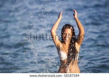 Cheerful girl splashing water towards the camera. Focus on the splash. - stock photo