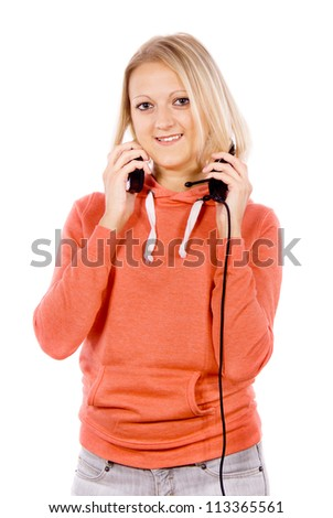 Cheerful girl stands with headphones isolated on white background - stock photo