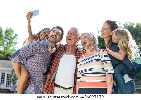 Cheerful girl taking selfie with multi-generation family in back yard - stock photo