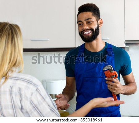 Cheerful girl thanking black professional plumber for work - stock photo