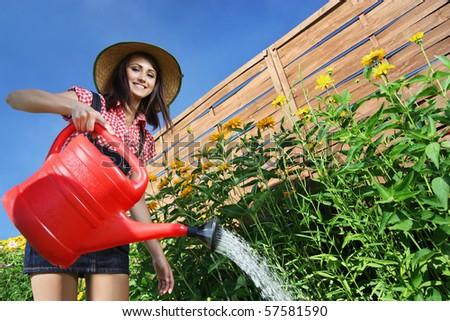Cheerful girl watering flowers - stock photo