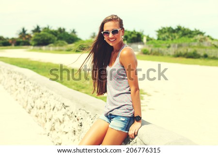 cheerful girl wearing trendy shorts and t-shirt walking at summer park. - stock photo