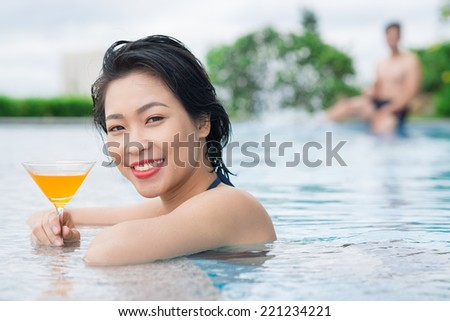 Cheerful girl with a cocktail at the edge of the swimming pool - stock photo
