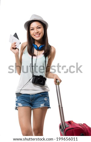 Cheerful girl with a suitcase showing airplane ticket - stock photo