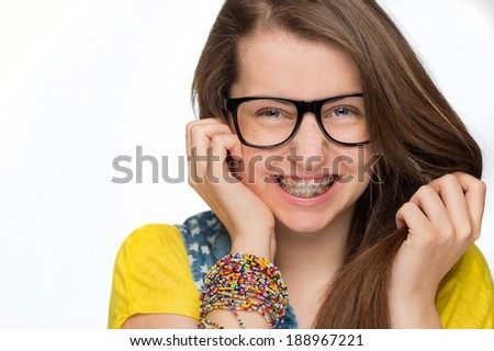 Cheerful girl with braces wearing geek glasses on white background - stock photo