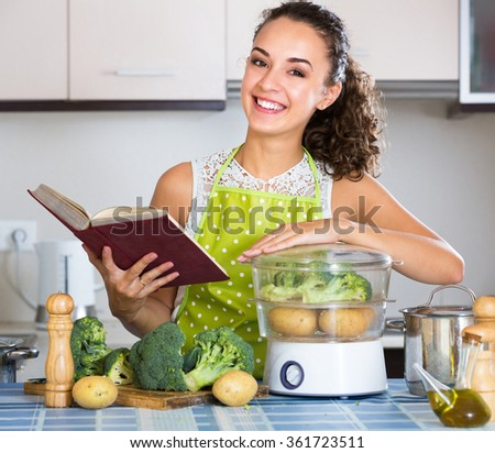 Cheerful girl with culinary book and steaming vegetables for healthy dinner  - stock photo
