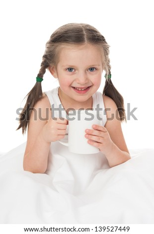 cheerful girl with cup in bed - stock photo