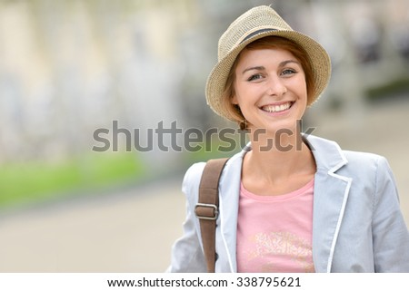 Cheerful girl with hat walking in town