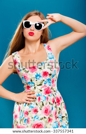 Cheerful girl, with long hair, wearing in white dress with floral pattern, and sunglasses, posing on blue background, in studio, waist up - stock photo