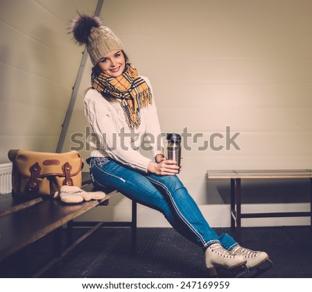 Cheerful girl with mug of hot drink in ice rink locker room  - stock photo