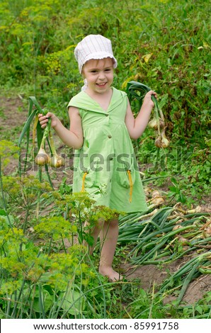 Cheerful girl with the crop of onions in the garden - stock photo