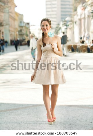 Cheerful girl witha lollypop walking down the street - stock photo