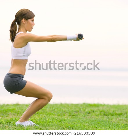 cheerful girl working out on the beach - stock photo