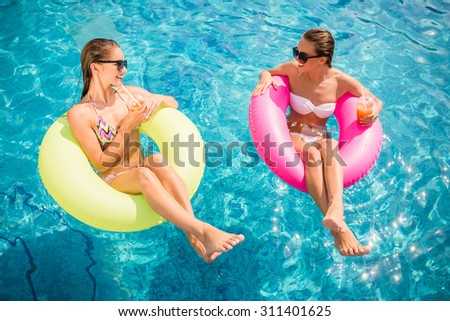 Cheerful girlfriends are having fun in swimming pool and drinking cocktail.