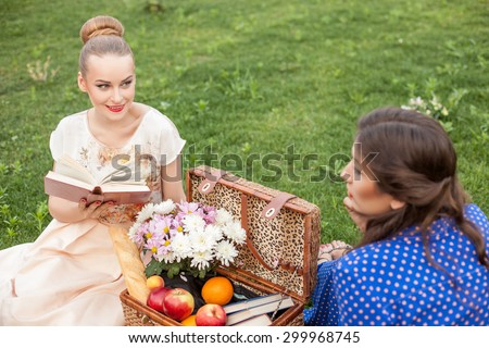 Cheerful girls are sitting on green grass and relaxing. One girl is reading aloud with enjoyment. She is smiling and looking at her friend. Another lady is listening to her with interest - stock photo