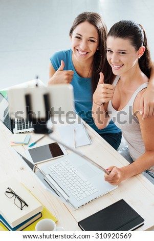 Cheerful girls at home sitting at desk and taking self portrait using a smart phone and a selfie stick, they are posing thumbs up - stock photo