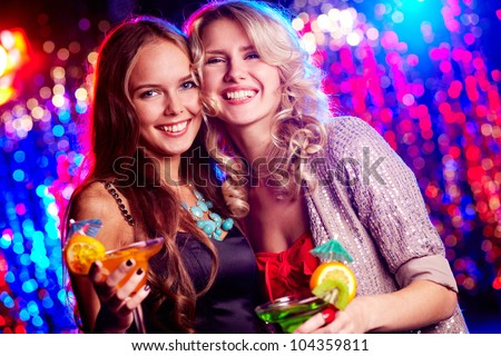 Cheerful girls dressed for party smiling at camera holding cocktails - stock photo