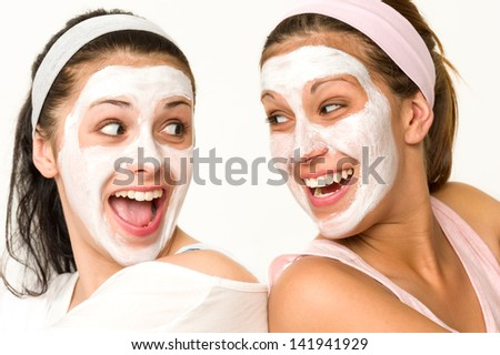 Cheerful girls having facial mask and laughing at each other - stock photo