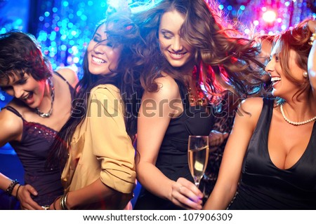 Cheerful girls living it up on the dance floor - stock photo