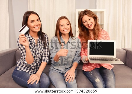 Cheerful girls showing laptop, bank card and gesturing