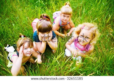 Cheerful girls sitting in the grass with backpacks - stock photo